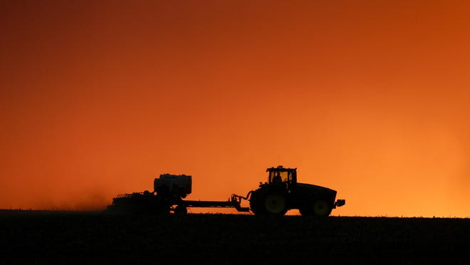 In this April 20, 2020, file photo, a farmer is silhouetted by the setting sun as a field is planted near Walford, Iowa. Thanks to the government paying nearly 40% of their income, U.S. farmers are expected to end 2020 with higher profit than 2019 and the best net income in seven years, the Department of Agriculture said in its latest farm income forecast.
