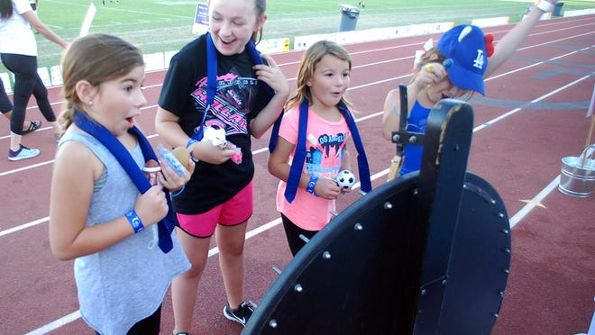 Jamison Blanchard, left, Presley Blanchard, Allison Acevedo and Sofie Craven react to Jamison's wheel spin win during the Visalia Relay for Life, Saturday.