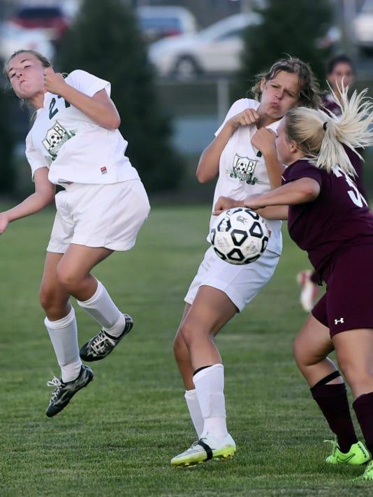 James Buchanan's Breanna Dukehart (27) heads a ball forward as Cass Martin (12) collides with Paige Miller (32) of Shippensburg on Tuesday. James Buchanan won the game, 4-0.