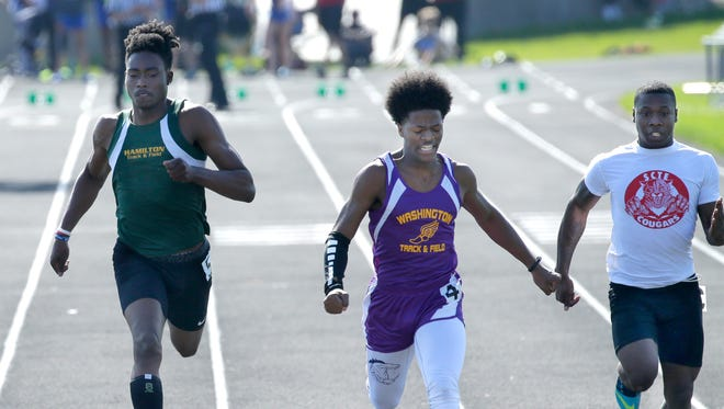Washington junior Elijah Johnson (center) wins the boys 100 meter dash.