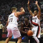 New Orleans Pelicans guard Jrue Holiday, center, finds himself trapped by Portland Trail Blazers center Meyers Leonard, left, and guard C.J. McCollum (3) during the first quarter of an NBA basketball game in Portland, Ore., Wednesday, Oct. 28, 2015.