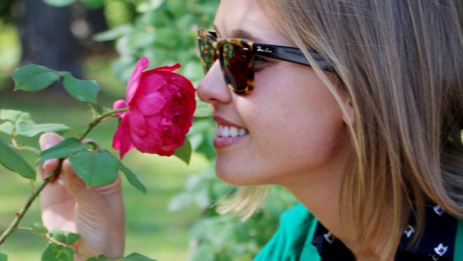 Ellina Laisovna, of Chelyafinsk, Russia, gets the scent of a rose during the It's All About the Roses Experience Tour at Gardens of the American Rose Center.