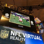 A football fan takes part in SAP's VR-based Quarterback Challenge at Super Bowl City in San Francisco.