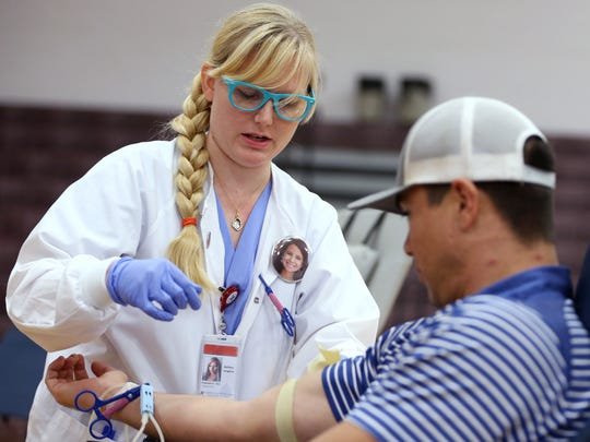 Wearing a button with the face of eight-year-old Hilari DeLeon, Bethany Langston (left), a phlebotomist with the Coastal Bend Blood Center, prepares Daniel Ramirez for a blood donation during a blood drive for Hilari on Wednesday, October 26, 2016 at Sinton High School. She was recently diagnosed with a rare blood disorder, Aplastic Anemia, which weakens her immune system and prevents her from doing the things she normally does, said her aunt, Susan Albright.