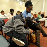 Josiah Marrero, 10, left, joins his mother Sharee McFadden and about 60 others at the budget prayer vigil at Logos Academy on Monday, Dec. 14, 2015. The group gathered in the hopes of reaching out in prayer for a successful passing of a budget for Pennsylvania.