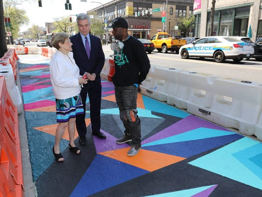 """Janet Langsam of ArtsWestchester, White Plains Mayor Thomas Roach and artist Wayne """"Wane One"""" Peterkin chat last Sunday by the mural he is painting on Mamaroneck Avenue. The artist was awarded a public art commission from ArtsWestcheter to paint the mural in celebration of its 20th anniversary."""