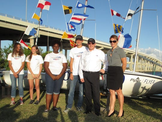 """Piper Aircraft representatives and Youth Sailing Foundation sailors recently commissioned the Piper Flyer.  Boat naming rights will again be available for bid at this year's """"Rock The Boat"""" fundraiser on March 18 at The Moorings."""