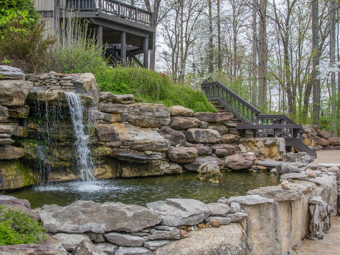 A stream flows into a 5,000-gallon waterfall that empties into a koi pond. The area overlooks Lake Monroe.