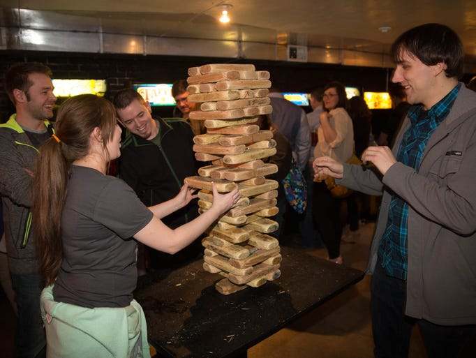 Jenna Clark, 28, pulls a Jinga block while playing