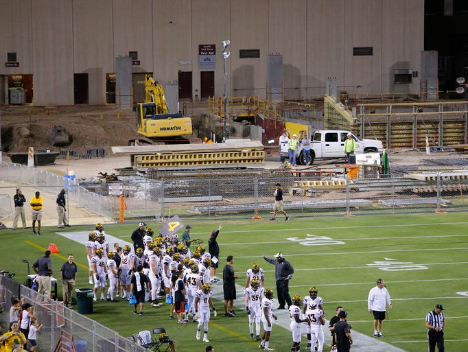 Construction workers watch the 2015 ASU spring football