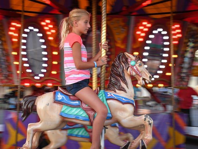 Lillian Longworth rides the carousel. The Winnebago