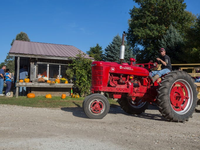 A tractor carries a wagon full of families visiting