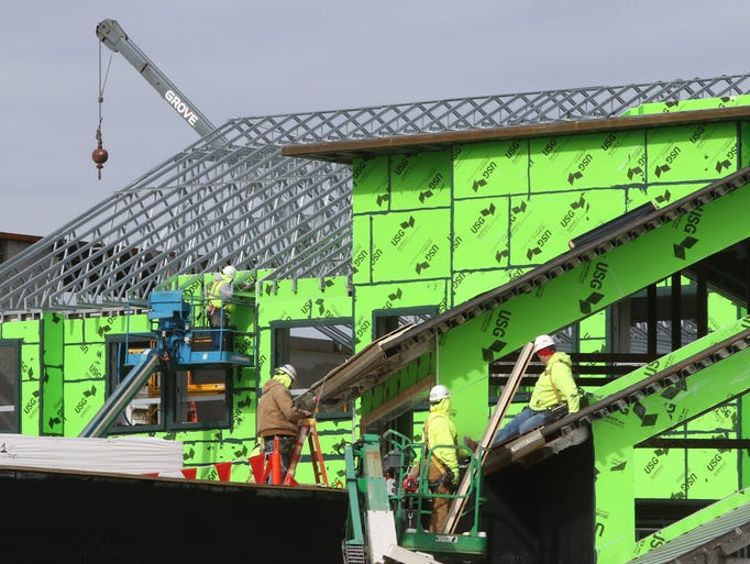 Contractors work on roofing and exterior finishing
