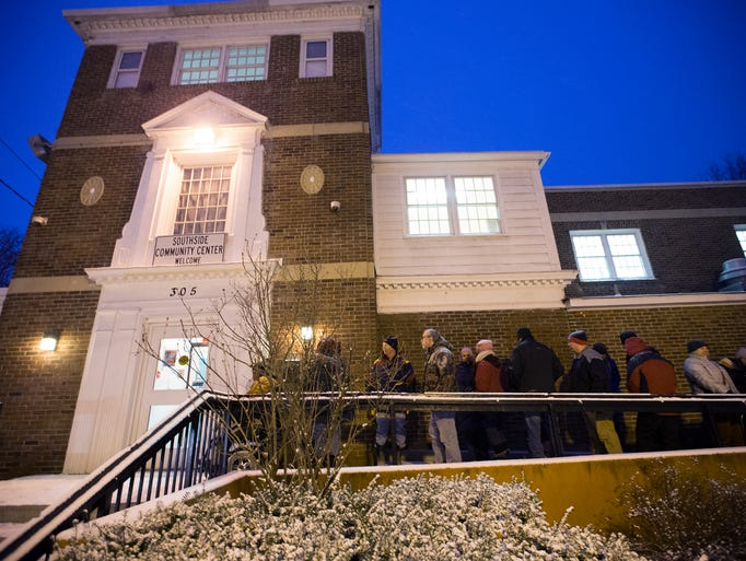 Residents wait in the cold for tickets to a town hall