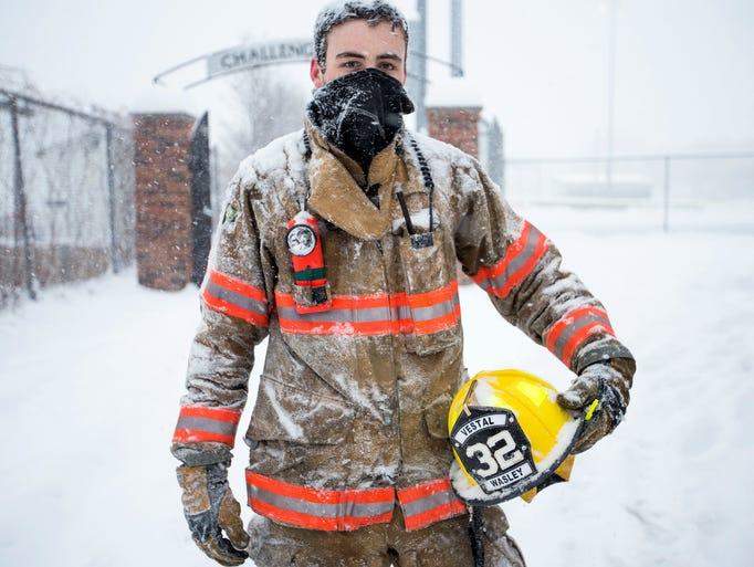 Vestal firefighter Carter Wasley stands near the scene