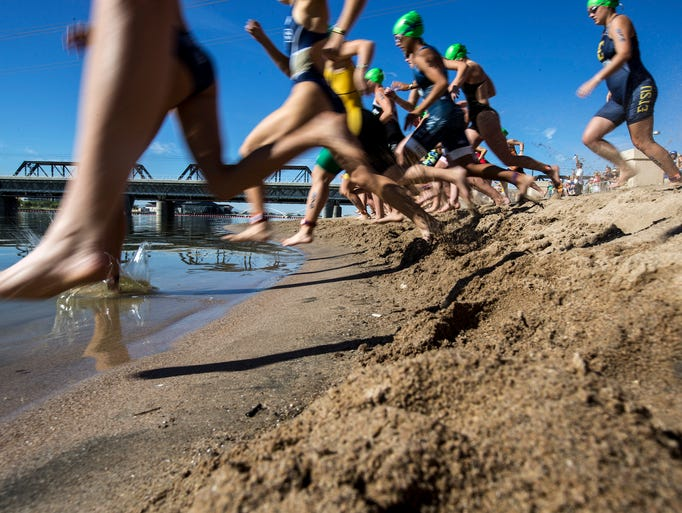 Athletes enter the water during the Women's Collegiate
