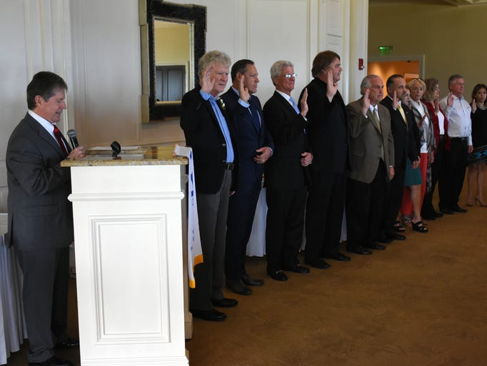 Bill Morris, left, swears in the new officers and directors.