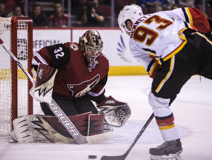 Flames center Sam Bennett attempts a shot against Coyotes
