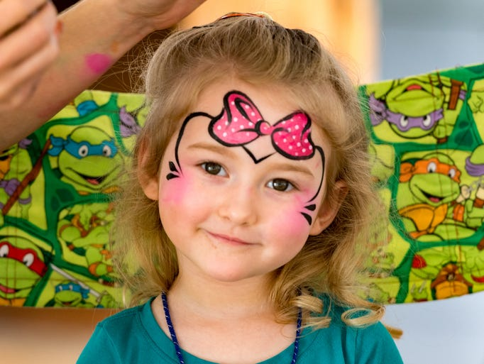 Adelynn Theriot having her face painted at the Spring