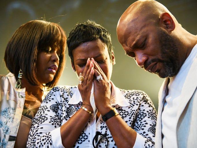 Queenie Freeman, middle, prays with Aventer Gray, left,