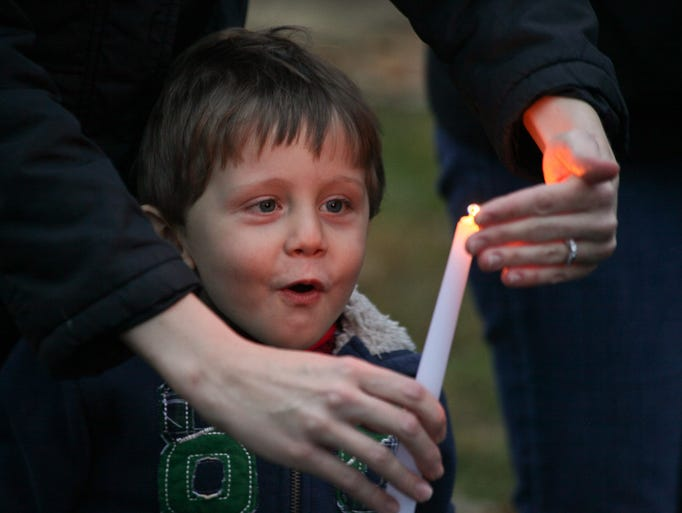 Gloria Kustes holds a candle for her son Caleb, during