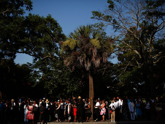 People wait in line to enter the funeral service where
