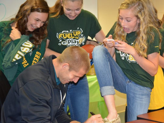 Adrianna Tupper and Natalie Deda watch   as Green Bay Packers wide receiver Jordy Nelson signs Haylie Novak's shoe, the only thing she had for him to sign.