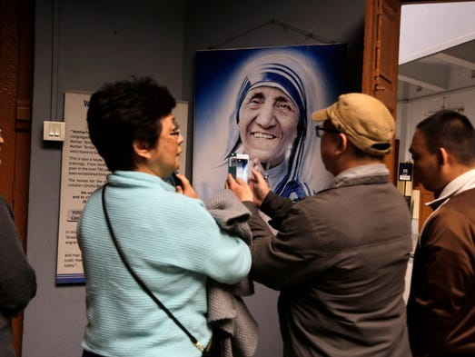 Visitors take photos of a portrait of Mother Teresa