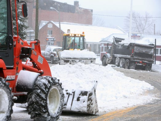 Machines clear piles of snow from Main Street in the
