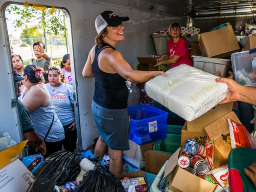 Kelly Olsen of Blaine, Minn. hands out donated supplies