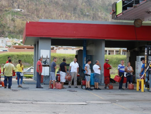 People stand on line to get gas at a gas station on