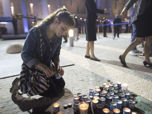 An Israeli woman lights a memory candle before passing