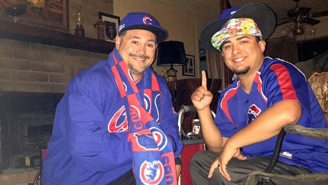 Sun-News sports editor Danny Udero and his son Daniel Udero Jr., celebrate after their Cubs won Game 7 of the World Series on Wednesday night.