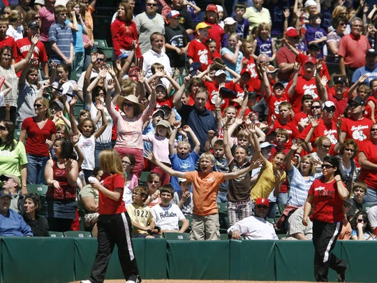 Indianapolis Indians fans in packed stands at Victory Field try to get the attention of Indians staff members throwing free T-shirts into the stands during the 11 a.m. game on Tuesday, May 19, 2009. The Indians beat the Syracuse Chiefs 5-4. Thousands of school children filled the stands on what turned out to be a beautiful day for the Indians' Baseball in Education promotion. (Charlie Nye / The Star).