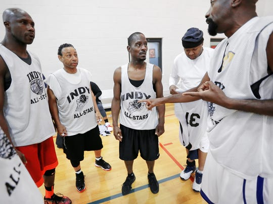 Indy All-Stars player C.J. Jordan, 56 of Indianapolis, middle, talks strategy with his teammates before a game against 2nd Chance at Washington Park on Saturday, Nov. 8, 2014. Jordan will play for the USA 55+ team in the FIMBA (Federation of International Masters Basketball Association) World Championships in Orlando, FL next year at the ESPN complex.
