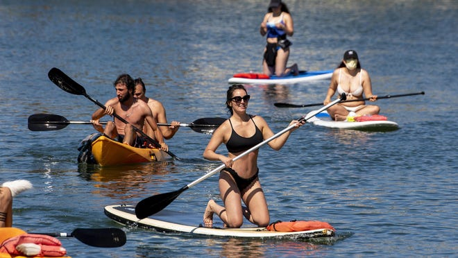 With beaches closed for the Fourth of July holiday weekend many took to kayaking and paddle boarding in Huntington Harbour in Huntington Beach on Sunday, July 5, 2020.