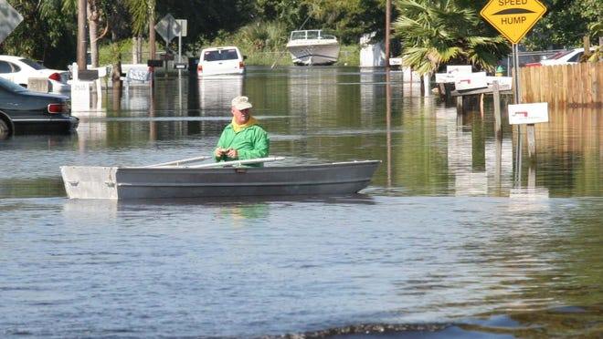 A boater snaps photographs on Stratford Drive in Cocoa, where many homes flooded from the torrential rain of Hurricane Wilma.