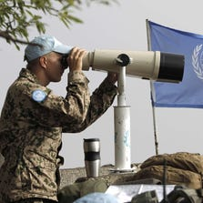 European members of the United Nations Disengagement Observer Force (UNDOF) use binoculars to watch the Syrian side of the Golan Heights on Aug. 30, 2014, in the Israeli-occupied Golan Heights, after Syrian rebel fighters took control of the Quneitra checkpoint between Israel and Syria.