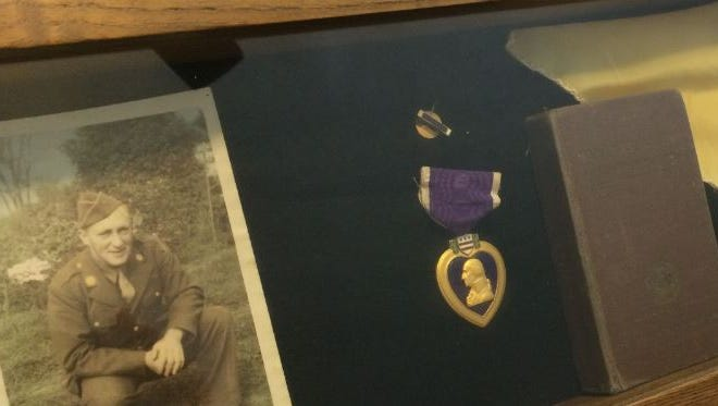Wayne Clark's daughter, Leah Woods, keeps some of her father's things in a display box, including his photo, Purple Heart and his Bible.