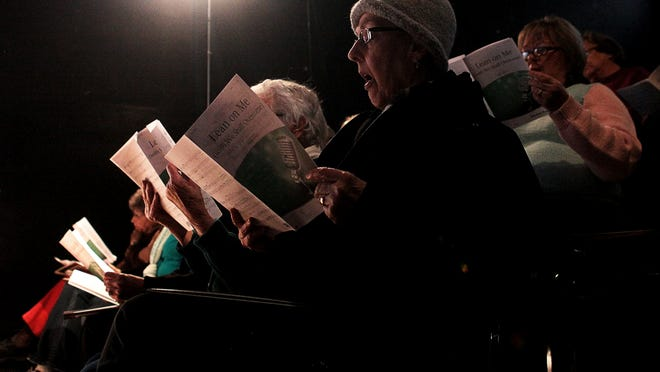The Survivor Voices choir rehearses at the Muncie Civic Theatre in March 2014.