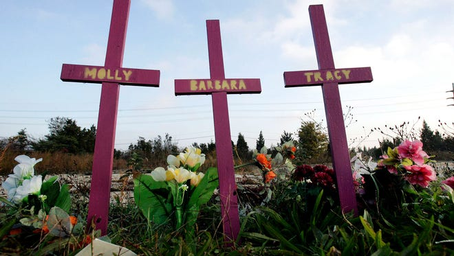 Three crosses stand, surrounded by flowers, in Egg Harbor Township, N.J., not far from the area where four Atlantic City-area prostitutes were found slain.