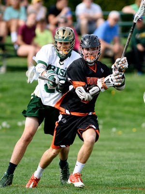 York Suburban's Matt LeCates, front, moves the ball across the field while York Catholic's Ryan Sewell defends during lacrosse action at York Catholic High School on Thursday. Dawn J. Sagert photo