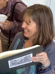 """Artist Jana Botkin with her book """"The Cabins of Wilsonia"""""""