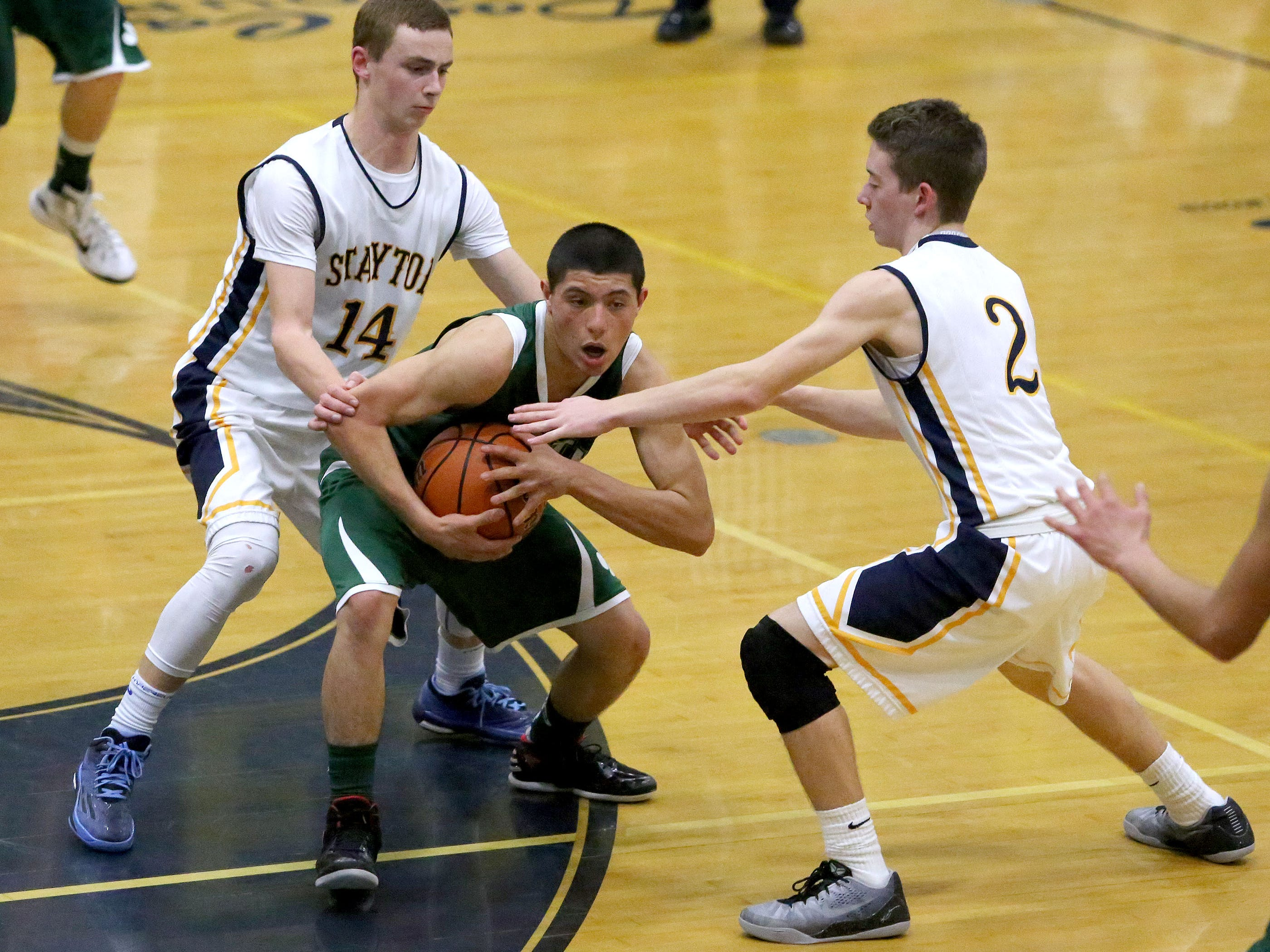 Stayton's Matt Lindeman (14) and Cade Nau (2) surround North Marion's Josiah Roman during their Oregon Western Conference game on Tuesday, Feb. 17 , 2015, in Stayton, Ore.