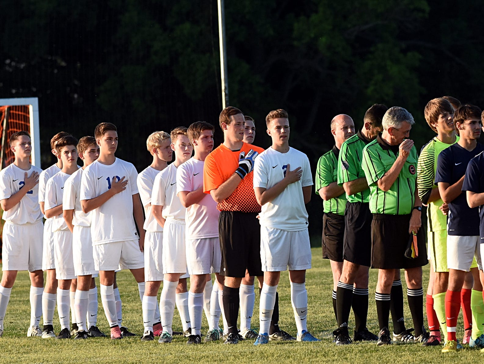 Players listen to the national anthem prior the start of Friday evening's District 9 A-AA Tournament championship match.