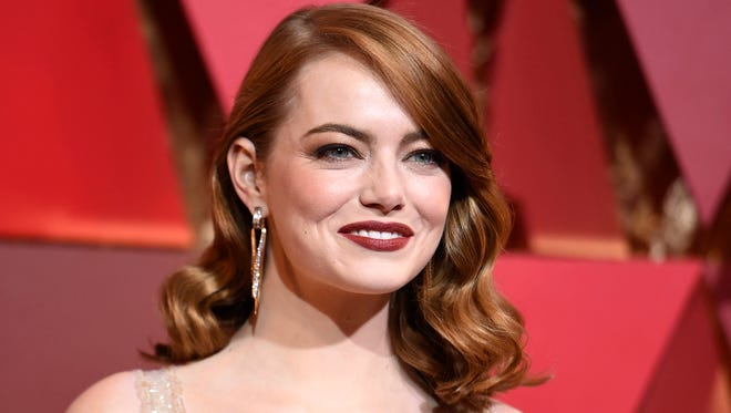 In this Feb. 26, 2017 file photo, actress Emma Stone arrives at the Oscars in Los Angeles. Stone says that male co-stars have taken pay cuts to ensure she received equal pay on films. Speaking to tennis great Billie Jean King in an interview published Thursday, July 6, in Out Magazine, Stone said the gesture to match has impacted what she's able to ask for in the future. (Photo by Richard Shotwell/Invision/AP, File)