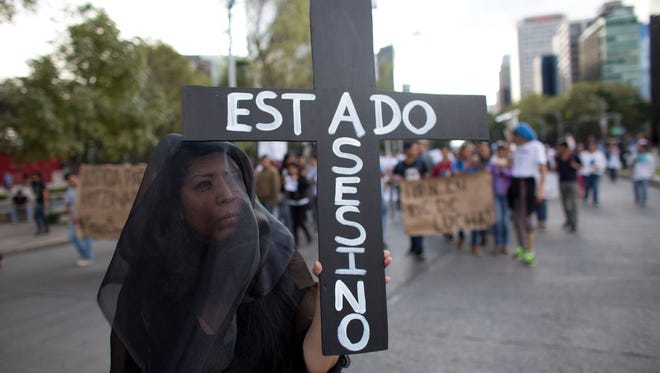 "A woman wears a black veil and carries a cross reading in Spanish ""Assassin State,"" as thousands march down one of the capital's main boulevards to demand that the government find the 43 students who disappeared in southern Guerrero State, in Mexico City, Wednesday, Oct. 8, 2014. Investigators still had no word on whether the 28 bodies found in a mass grave over the weekend included any of the missing students, who disappeared after two attacks allegedly involving Iguala police in which six people were killed and at least 25 wounded. (AP Photo/Rebecca Blackwell)"