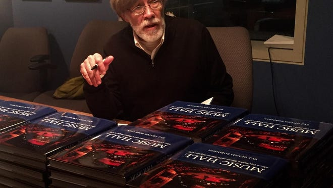 """Historian J. Dennis Robinson signs copies of his latest book, """"Music Hall,"""" at a Writers at the Loft event."""