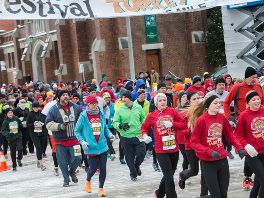 People begin their Thanksgiving Day with a walk or run through the streets in Oshkosh for the seventh annual Festival Foods Turkey Trot in this 2014 file photo.