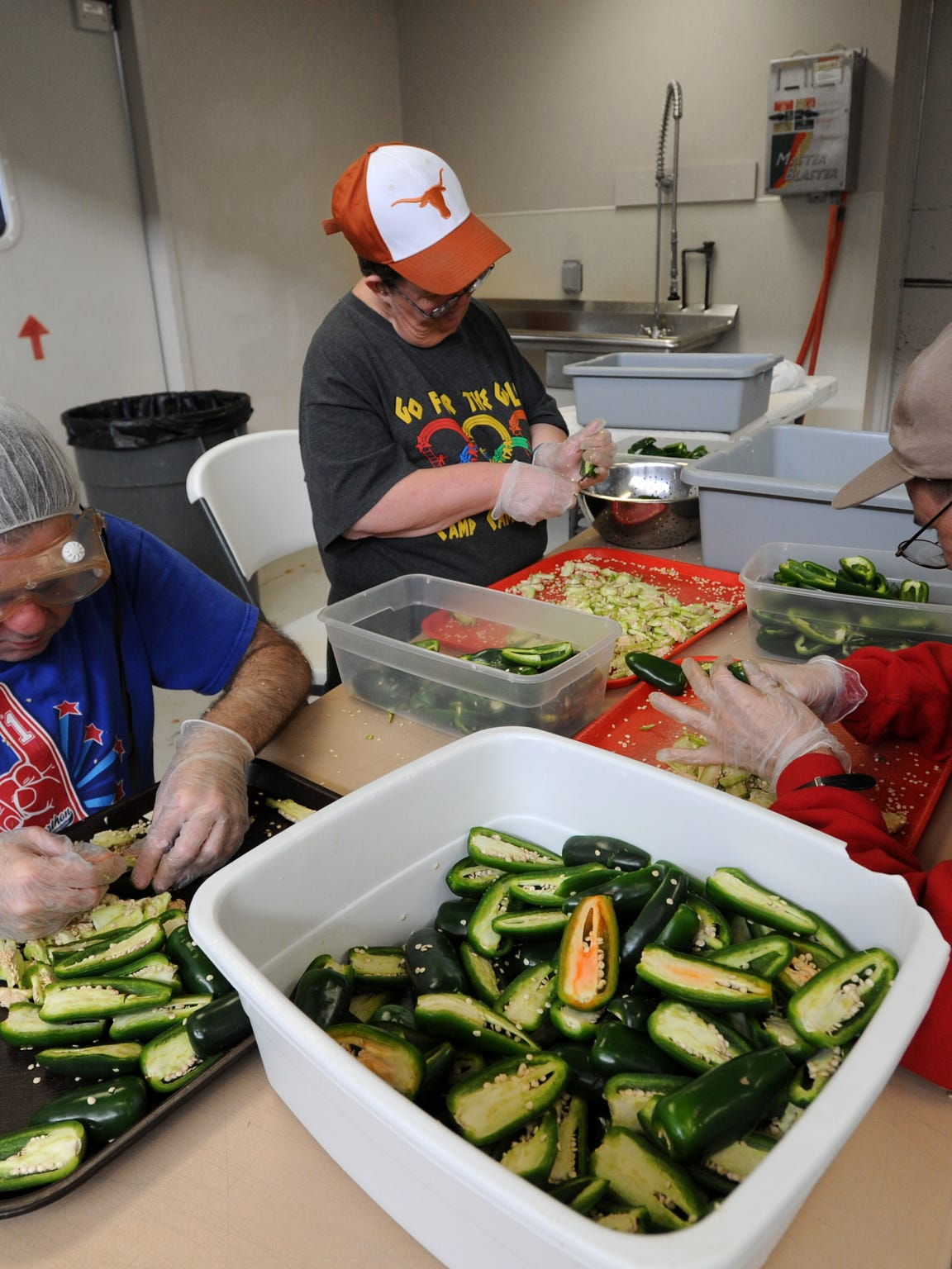 Allan Madding, left, Gina Graves, center, and Jeremy Antilley, right, remove seeds from jalapeno peppers at  Disability Resources Inc. in October 2012.